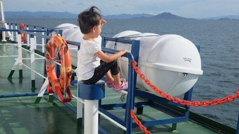 Un enfant regardant le large à bord d'un ferry indonésien