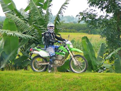 Un motard en Kawasaki KLX dans des rizières en Indonésie